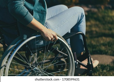 Close up of a young woman in a wheelchair while walking in a park on a sunny day. Recovery and healthcare concepts.
