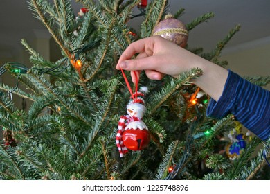 Close up of a young woman's hand and arm as she decorates a Christmas Tree with a happy snowman ornament