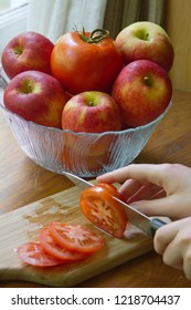 Close up of a young woman's hand slicing beefy red tomatoes on a wood cutting board with a sharp knife, with a glass bowl of apples and one tomato in the background