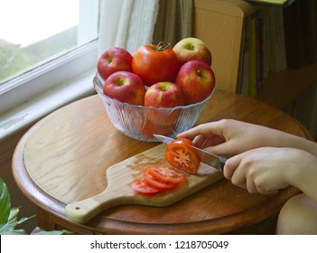 Close up of a young woman's hand slicing beefy red tomatoes on a wood cutting board with a sharp knife, with a glass bowl of apples and tomatoes in the background