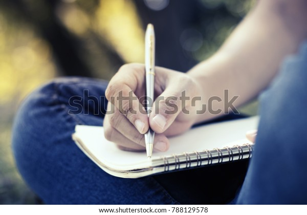 close up young women writing on notebook in park, concept in education and knowledge