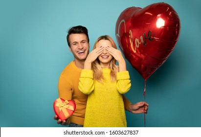 Close your eyes. Close up photo of a charming man, who is laughing and holding a red gift box and a heart-shaped balloon in his hands, while his girlfriend is standing with her eyes closed.