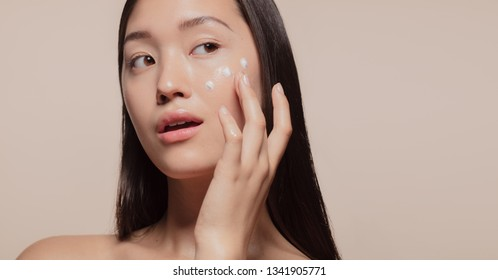 Close up of a youthful female model applying moisturizer to her face. Young korean woman applying moisturizer cream on her pretty face against beige background.
