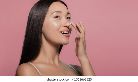 Close up of a youthful female model applying moisturizer to her face. Young korean woman putting moisturizer cream on her pretty face against pink background.