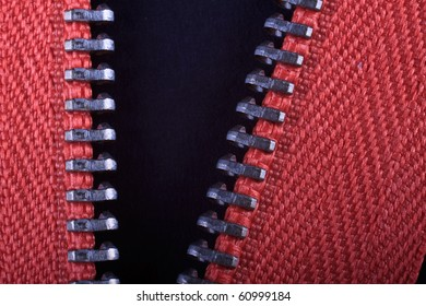 A close up of a zip undone against a black background