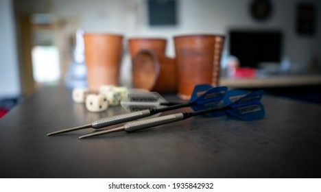 A close up of zwo darts in the foreground and a game of dice with leather cups in the background on a black counter.