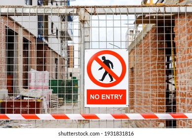 Closed access door to the construction site of a building, with a no-entry sign.