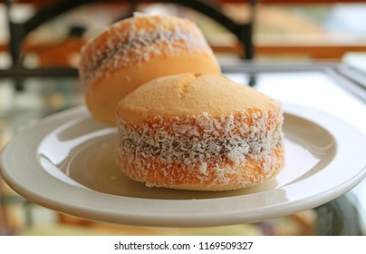 Closed up Alfajores sweets, traditional Latin American sweetened milk filling cookies served on white plate