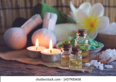 Closed up aroma gel in glass bottle put together with couple of aroma candle,massage compress,towel,scrub salt,and decorated with frangipani or plumeria flower,in dark night light at spa shop
