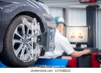 Closed up of an auto wheel : computer wheel alignment. Balancing tire wheel machine. Tyre assembling. Tyre balancing of modern car in workshop.