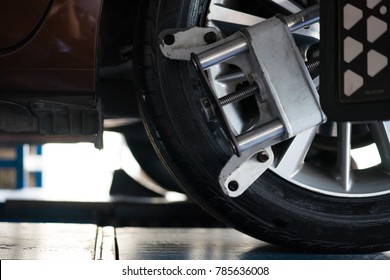 Closed up of an auto wheel that is undergoing wheel alignment with computerized. Stand balancing tire wheel machine. Tyre assembling. Tire balance - Car service concept