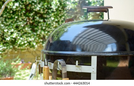 A closed barbecue during pulled pork cooking day, with tools