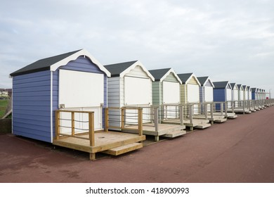 Closed up beach huts at Lytham St Annes.  The weather is overcast, with only hints of blue in the sky.