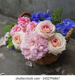 closed up beautiful flower in rattan basket with concrete background