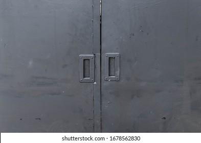 A closed black iron door.