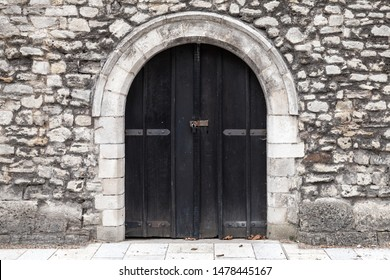 Closed black wooden door in old stone wall, background photo texture