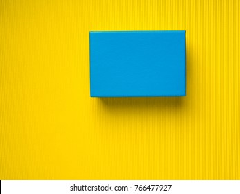 Closed Blue gift box on yellow background