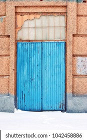 Closed blue painted door, pink plaster on wall, grunge background, winter snowy street, vertical