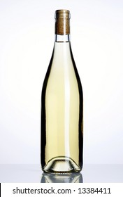 Closed bottle of white wine on white background