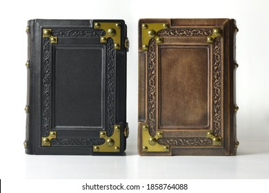 Closed brown and black leather books with ornate frame and metal corners stand up one to another