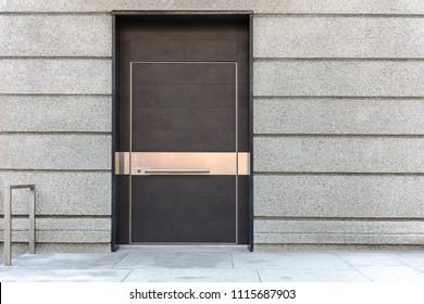 closed brown metal door on grey stone wall of building facade