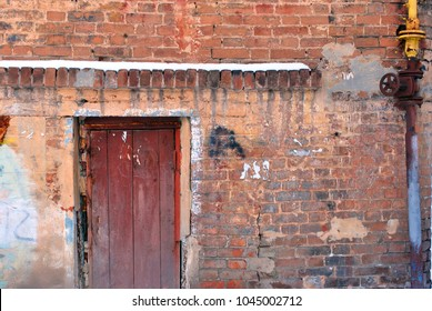 Closed brown painted door, red brick wall with yellow rusty gas pipe with spigot, grunge horizontal background