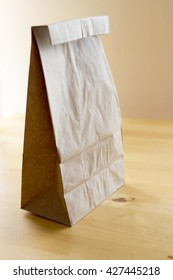 Closed brown paper lunch bag on wood table