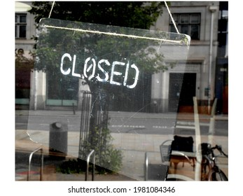 Closed for business sign in window with reflection of empty streets
