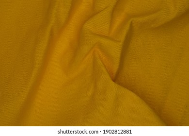 closed up clumped yellow canvas texture, the cross of natural fibers makeup to roughly clothes, wave and folding pattern background