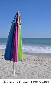A closed colorful beach umbrella at the seashore.