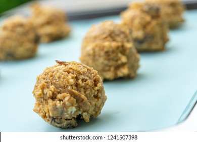Closed up of cookie dough on baking sheet, brown hazelnuts, raisin and oatmeal put in scoop before put in the oven.