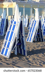 Closed deckchairs in a beach at sunset