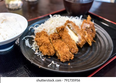 Closed up deep fried pork cutlet coated with flaky panko bread crumb and stuffed with cheese, Pork Tonkatsu over shredded cabbage, Japanese menu set served with rice.