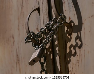 Closed doors with metal chain and lock, close-up