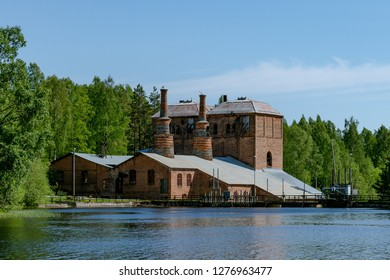 Closed down and abandoned steel mill or ironworks by a lake on the Swedish countryside, on a beautiful summer day with sunshine and blue sky