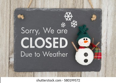 Closed due to weather sign, A chalkboard sign with a snowman with text Closed due to weather on weathered wood