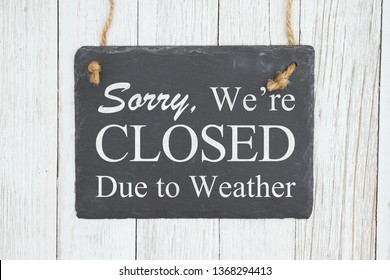Closed due to weather sign, Sorry we're Closed text on a hanging retro chalkboard on weathered whitewash textured wood