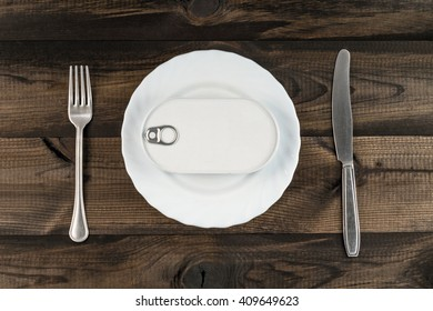 Closed easy open fish can with the pull tab on white plate with fork and butter knife on wooden table