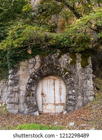 A closed entrance to a small service tunnel has interesting features (stone arch and lots of vegetation). Who might live there ?
