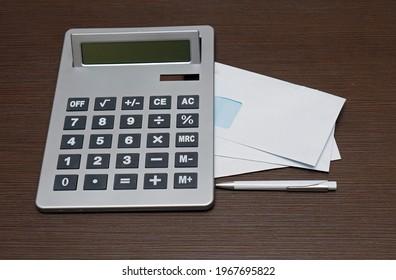 Sobres cerrados con impuestos de facturas y otros gastos con una calculadora grande para calcular la suma total