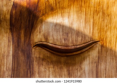 a closed eye carved in a wooden wall