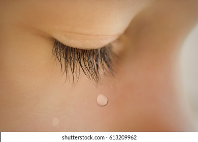 Closed eyelid child close up with a tear on the eyelashes. A tear runs down his cheek. The baby is crying