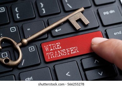 Closed up finger on keyboard with word WIRE TRANSFER