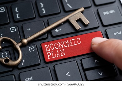 Closed up finger on keyboard with word ECONOMIC PLAN
