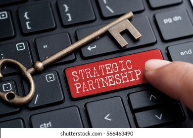 Closed up finger on keyboard with word STRATEGIC PARTNERSHIP