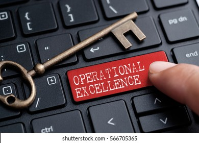 Closed up finger on keyboard with word OPERATIONAL EXCELLENCE