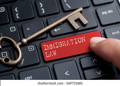 Closed up finger on keyboard with word IMMIGRATION LAW