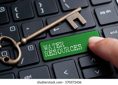 Closed up finger on keyboard with word WATER RESOURCES
