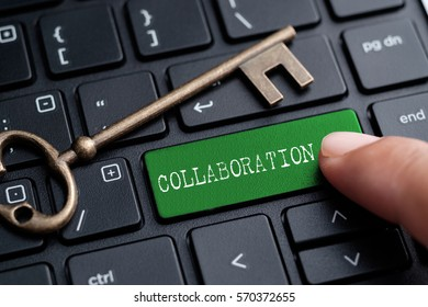 Closed up finger on keyboard with word COLLABORATION
