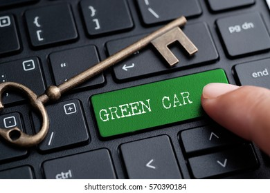 Closed up finger on keyboard with word GREEN CAR